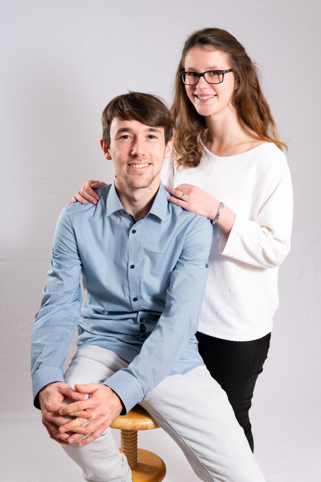 Junger Mann in blauem Hemd sitzt auf Stuhl neben junger stehender Frau, die sich an ihn lehnt