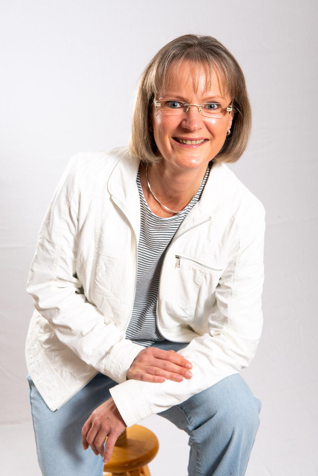 Frau mit Brille und weißer Jacke sitzt vor weißem Hintergrund