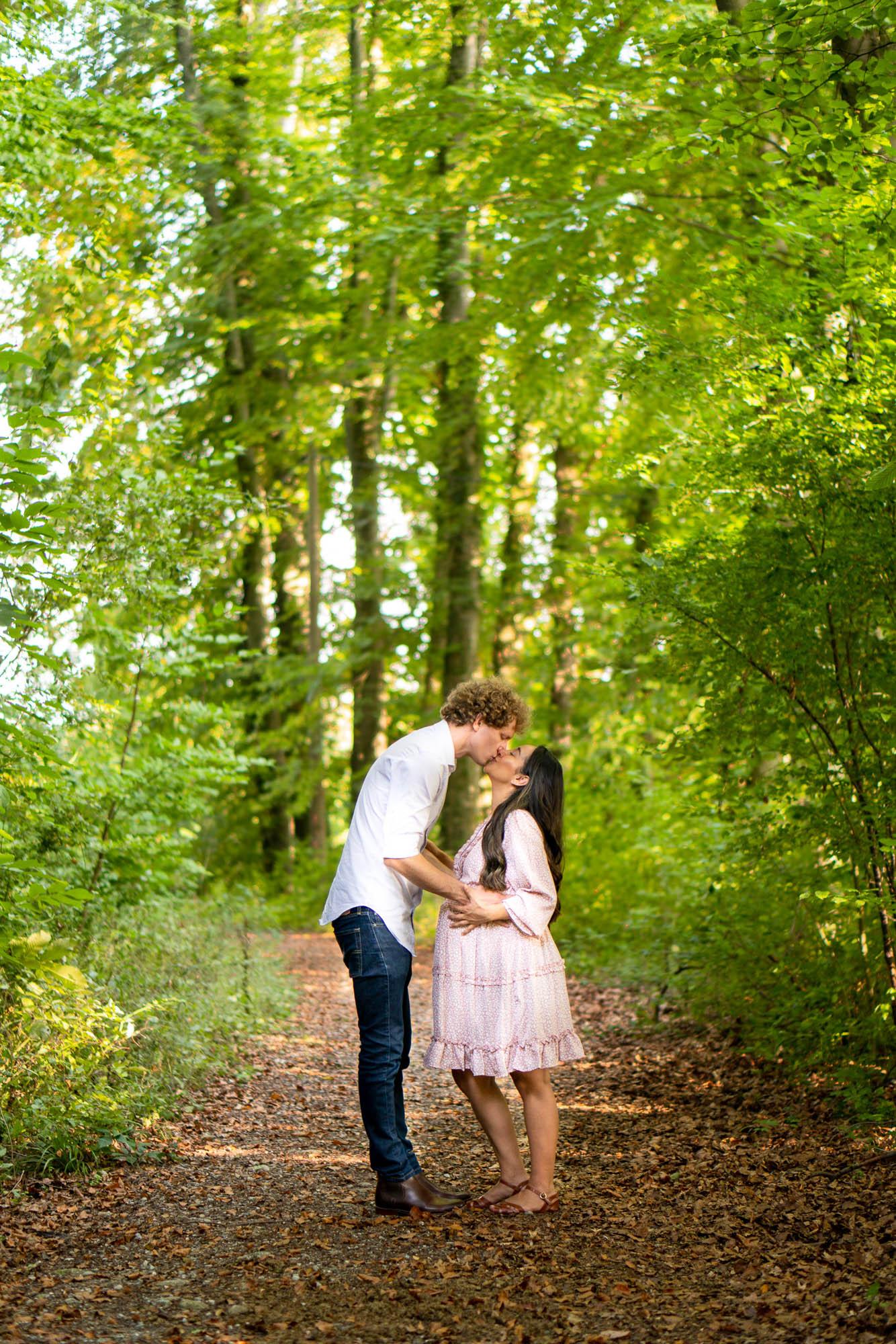 schwangere Frau und ihr Mann küssen sich im Wald