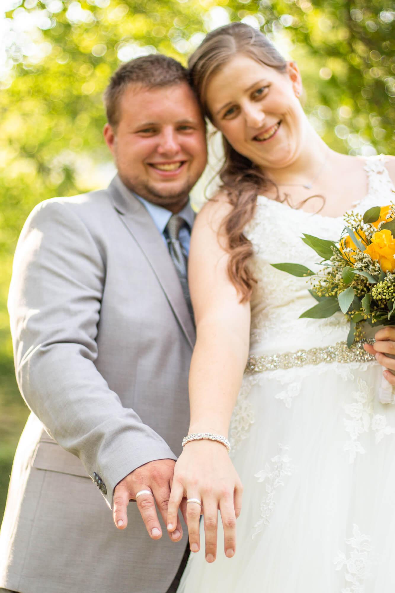 frisch verheiratetes Ehepaar zeigt ihre Eheringe