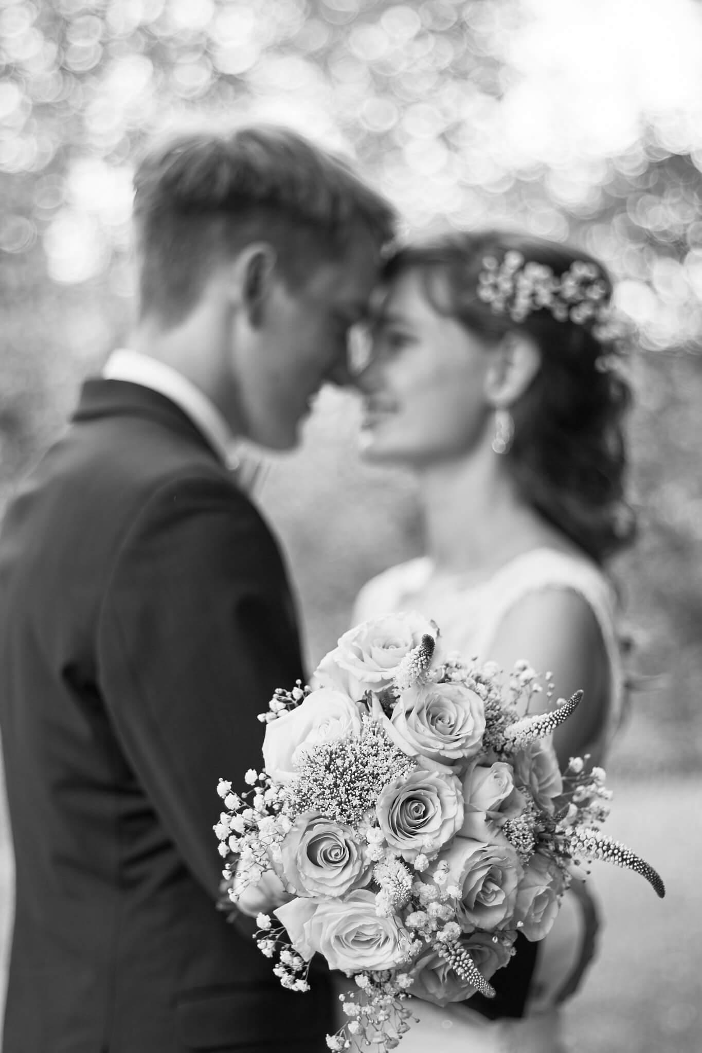 Mann berührt die Stirn seiner Frau mit Brautpaarstrauß