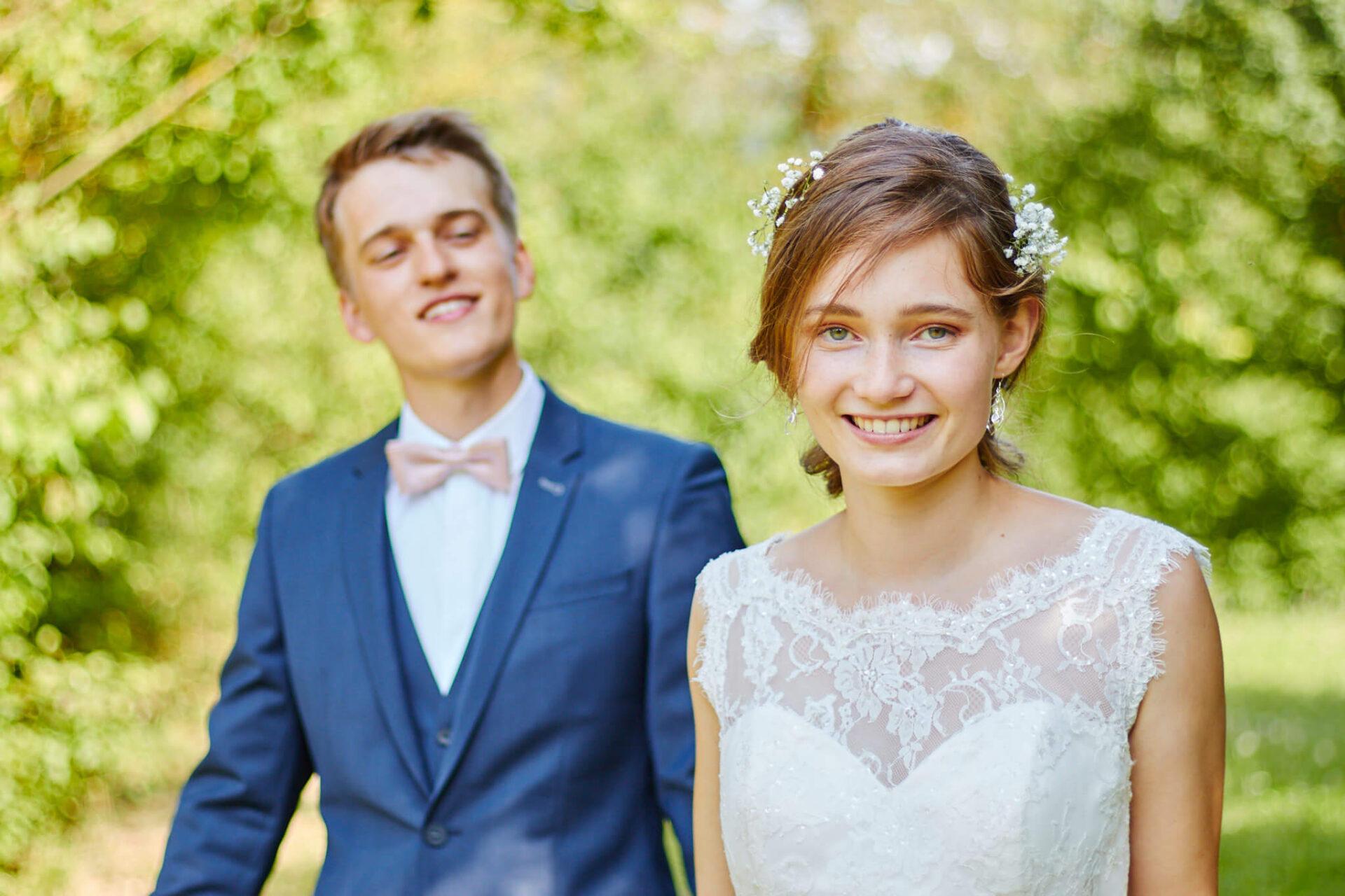 Frau im Hochzeitskleid läuft mit Mann in der Natur
