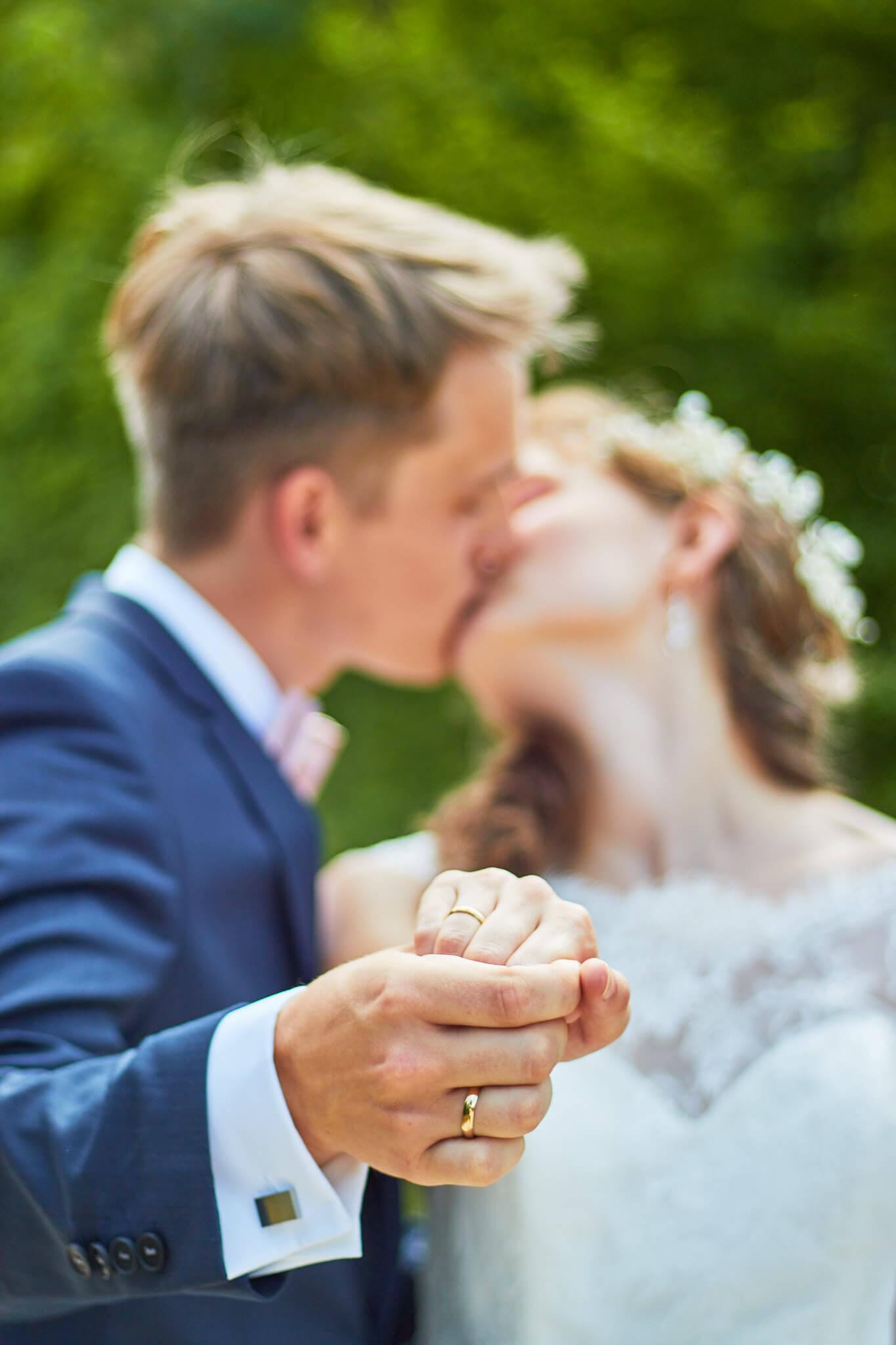 frisch verheiratetes Ehepaar küsst sich und hält Händchen
