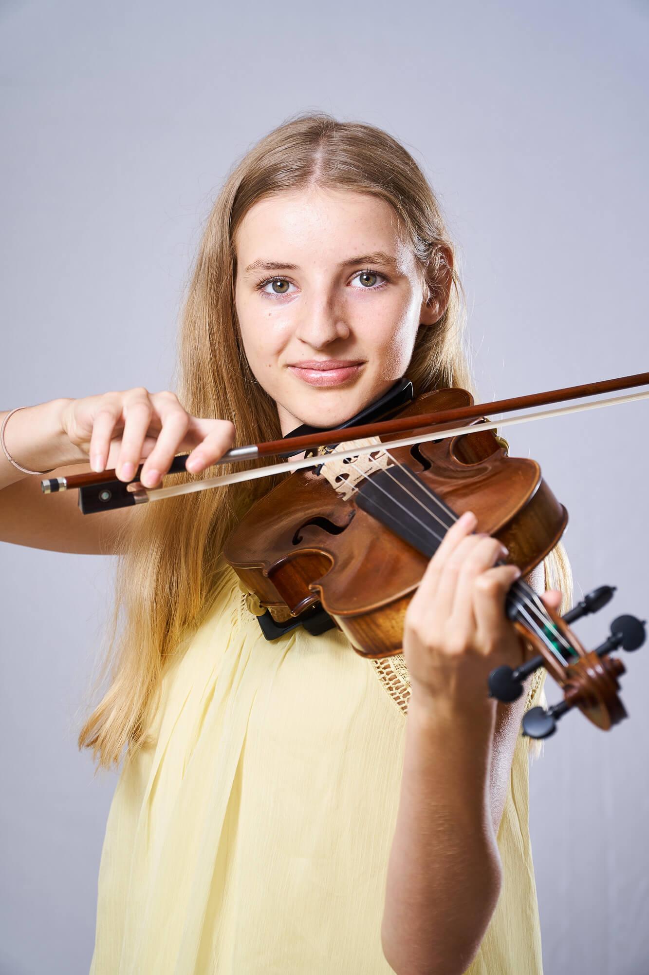 blondes Mädchen mit gelben Kleid spielt Geige