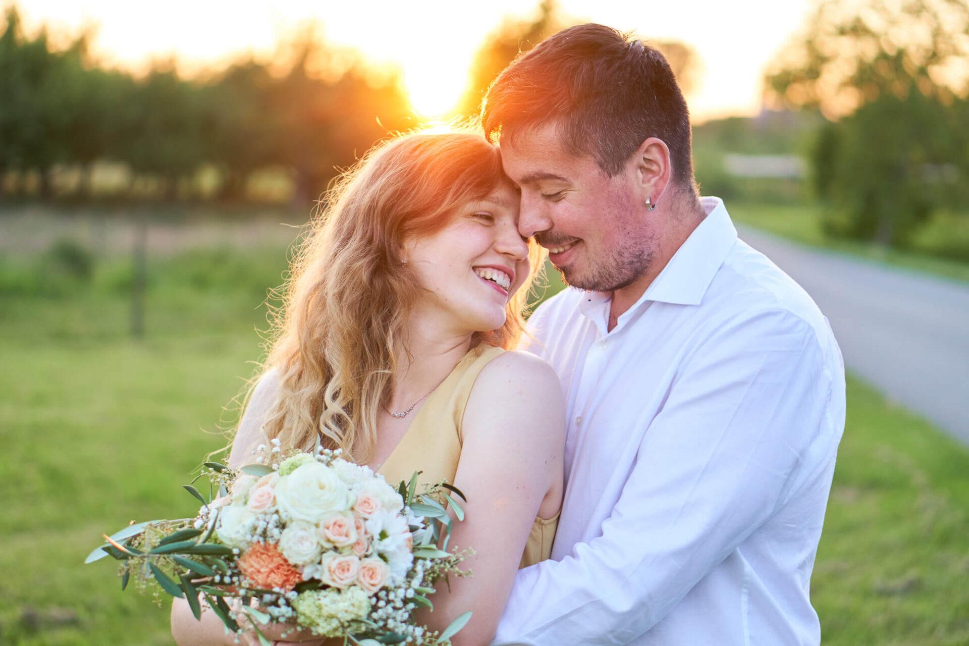 Mann im Hemd lächelt seine Frau im Kleid an