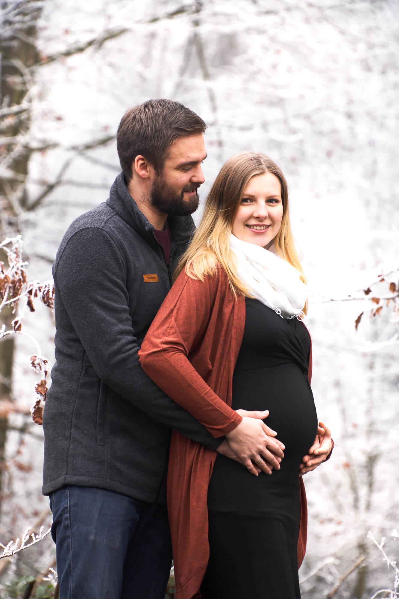 Mann hält den Bauch seiner schwangeren Frau