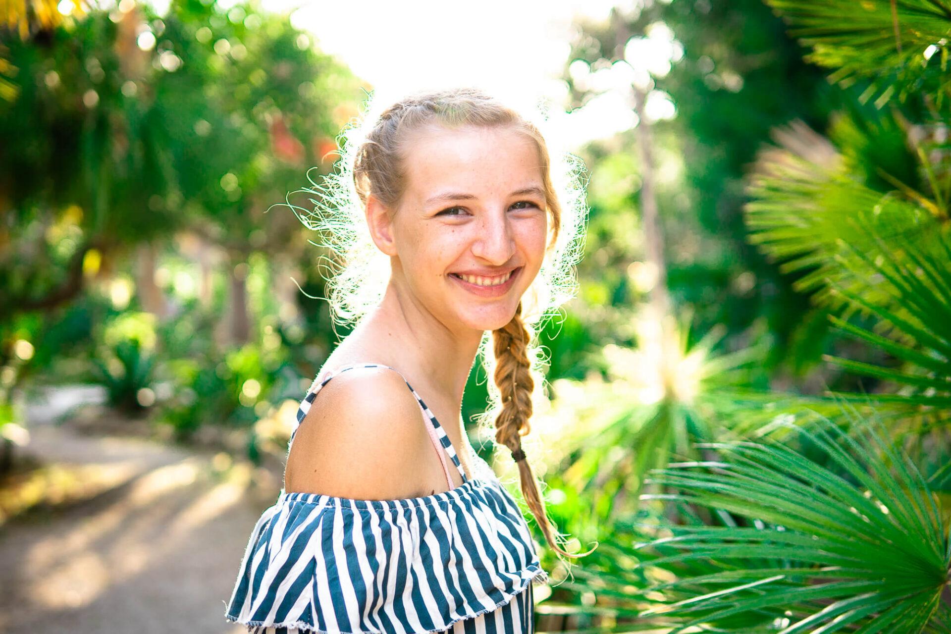 lachendes Mädchen ist umgeben von Palmen