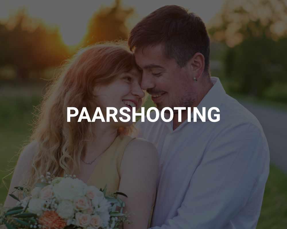 Junges, verliebtes Ehepaar mit Blumen vor Sonnenuntergang